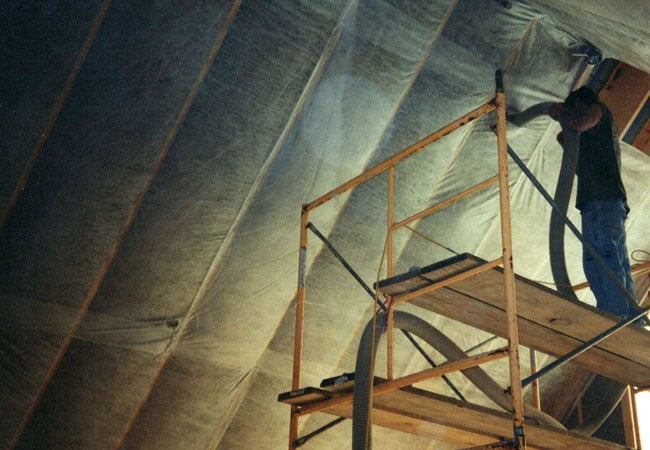 worker installing insulation in the attic